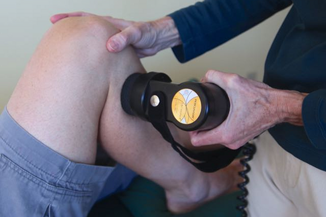 Image of the application of percussion therapy to the lower extremity.